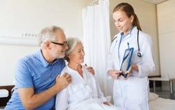 Hög kvinna och doktor med minnestavlaPC på sjukhuset Royaltyfria Bilder