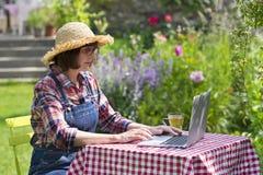 Hög kvinna som använder en bärbar datordator i hennes trädgård Fotografering för Bildbyråer