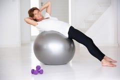 Hög kvinna som använder idrottshallbollen Fotografering för Bildbyråer
