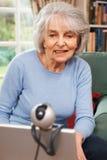 Hög kvinna som använder webcamen för att tala med familjen Arkivfoto