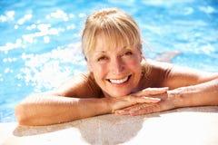 Hög kvinna som har gyckel i simbassäng Royaltyfri Fotografi