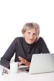 Hög kvinna som har problem med hennes dator Arkivbild