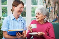 Hög kvinna som hemma besökas av vårdare Arkivbild