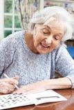 Hög kvinna som hemma kopplar av med korsordpusslet Royaltyfria Foton