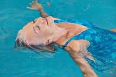 Hög kvinna som kopplar av i simbassäng Royaltyfria Bilder