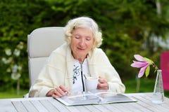 Hög kvinna som kopplar av i trädgården Royaltyfri Fotografi