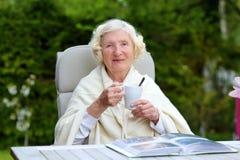 Hög kvinna som kopplar av i trädgården Royaltyfri Bild