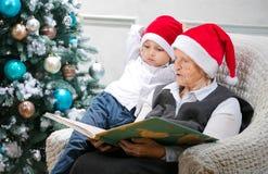 Hög kvinna som läser en bok till hennes sonson Royaltyfria Bilder