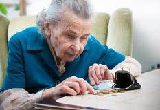 Hög kvinna som räknar pengar Arkivbilder