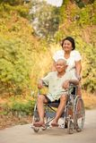 Hög kvinna som skjuter henne rörelsehindrad hasband på rullstolen Royaltyfri Bild