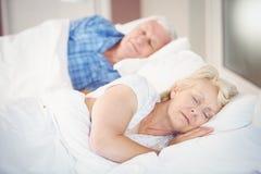 Hög kvinna som sover förutom make på säng Royaltyfri Bild
