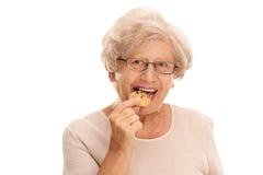 Hög kvinna som äter en kaka Royaltyfria Foton