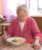 Hög kvinna som äter soppa Royaltyfri Foto