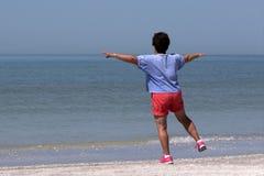 Hög kvinna som övar på en strand Arkivfoto