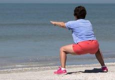 Hög kvinna som övar på en strand Royaltyfri Bild
