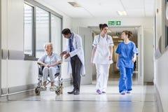 Hög kvinnlig patient för doktorer sjuksköterska i sjukhuskorridor Arkivbild