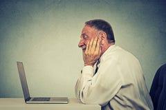 Hög man som använder nyheterna för email för bärbar datordator läs- Royaltyfri Fotografi