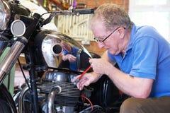 Hög man som arbetar på tappningmotorcykeln i garage Royaltyfri Bild