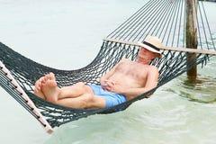 Hög man som kopplar av i strandhängmatta Royaltyfria Bilder