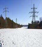 hög-spänning överföringslinje med elektricitetspyloner Arkivfoto