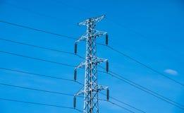 Hög spänningsstolpe eller maktöverföringslinje torn och blå himmel Fotografering för Bildbyråer