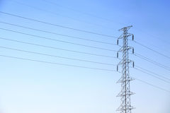 Hög spänningsstolpe eller maktöverföringslinje torn och blå himmel Arkivfoto