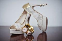 Höga häl som gifta sig skor och armbandet på tabellen Brud i den vita klänningen Fotografering för Bildbyråer