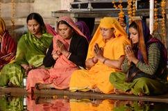 Höga kvinnor utför pujaen - rituell ceremoni på den heliga Pushkar Sarovar sjön, Indien Arkivfoton