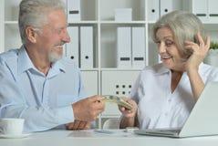 Höga par med bärbara datorn och pengar Royaltyfri Bild