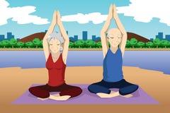 Höga par som gör yogaövning Arkivbild
