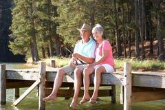 Höga par som har roligt fiske Fotografering för Bildbyråer