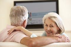 Höga par som hemma håller ögonen på Widescreen TV Royaltyfri Fotografi