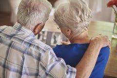 Höga par som håller ögonen på deras gamla foto Arkivfoto