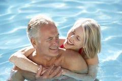 Höga par som tillsammans kopplar av i simbassäng Arkivfoton
