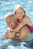 Höga par som tillsammans kopplar av i simbassäng Fotografering för Bildbyråer