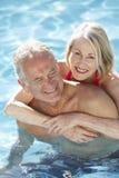 Höga par som tillsammans kopplar av i simbassäng Royaltyfri Foto