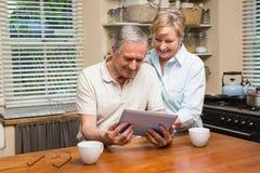 Höga par som tillsammans ser minnestavlaPC Arkivfoton