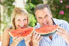 Höga par som tycker om skivor av vattenmelonen Royaltyfri Fotografi