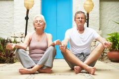 Höga par som utomhus mediterar på vård- Spa Royaltyfria Bilder