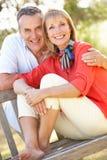 Höga par som utomhus sitter på bänk Royaltyfri Foto