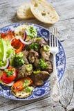 Hígado de pollo frito y verduras asadas a la parrilla - pimienta roja, calabacín, ensalada verde Imagenes de archivo