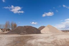 Högar av grus på konstruktionsplatsen under ljus blå himmel Arkivbild