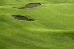 Hügelfeld des grünen Grases des Golfplatzes mit Löchern Stockbild