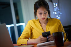 Högskolestudenten Studying At Night skriver meddelandet på telefonen Royaltyfri Fotografi
