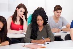 Högskolestudenter som skriver på skrivbordet Royaltyfri Bild