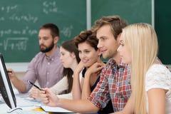Högskolestudenter som studerar genom att använda en dator Royaltyfria Bilder