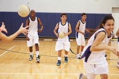 Högstadiumstudenter som spelar den Dodge bollen i idrottshall Arkivfoto