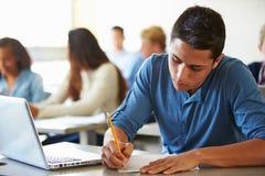 Högstadiumstudenter som tar provet i klassrum Arkivbild