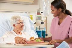 Högt kvinnligt tålmodigt mål för sjuksköterskaportion i sjukhussäng Arkivfoton