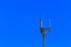 Högväxt stort, mobiltelefontorn mot en blå himmel Royaltyfri Bild